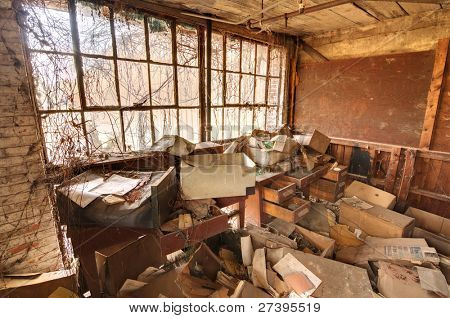Old office in a factory, abandoned, ransacked, and overgrown with vines.