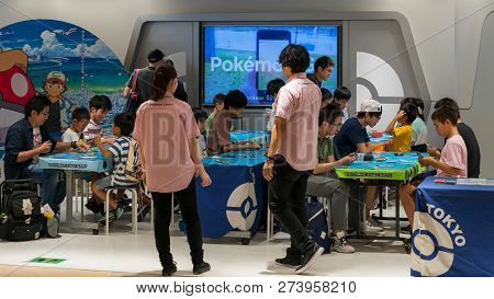 Tokyo, Japan - August 2018: Parents With Their Children Playing Pokemon Branded Arcade Video Games A