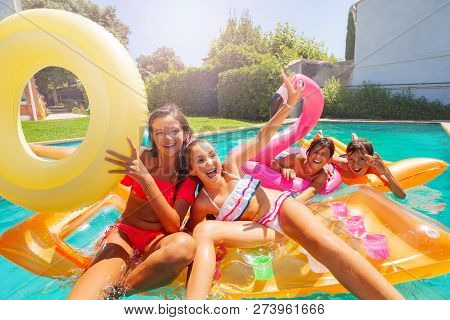 Cute Teens Playing With Swimming Floats In Pool