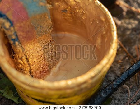 Plastic Bucket With Old Bath Puff, Close Up View. Bucket With Golden Paint On The Ground. Vintage Ba