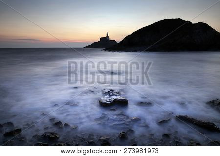 Dawn And A Long Exposure At High Tide Over A Silhouette Of Mumbles Lighthouse In Swansea, South Wale