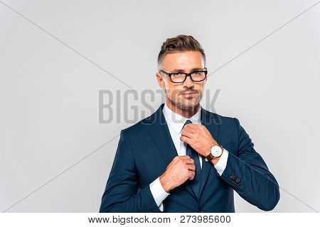 Portrait Of Handsome Businessman In Suit And Glasses Tying Tie Isolated On White