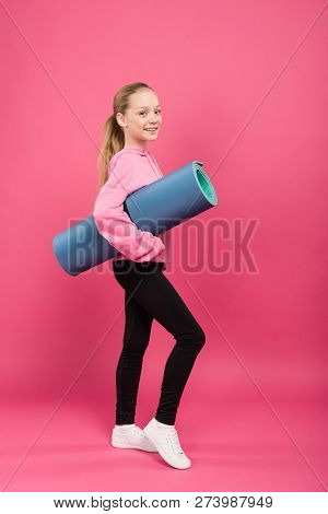 blonde youngster in sportswear holding fitness mat, isolated on pink poster