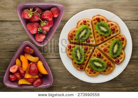 Wafers With Kiwi And Cranberries On A Wooden Background. Waffles On A Plate Top View