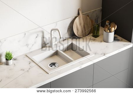 Top View Of White Marble Kitchen Sink Standing On Gray Countertop In Room With White Walls. Wooden R
