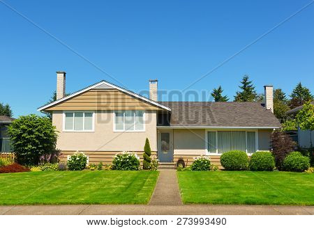 Average Residential House In Perfect Neighbourhood. Family House With Big Yard And Green Lawn In Fro