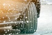 Close up detail car wheel with new black rubber tire protector on winter snow covered road. Transportation and safety concept. poster