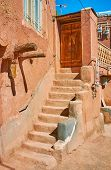 Adobe staircase leads to the house entrance with old wooden door, Abyaneh, Iran. poster