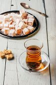 Tea in arabic glass with turkish delight Rahat Lokum over wooden surface poster