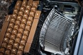 Old and broken typewriter, obsolete, with the blades and the QWERTY keyboard remaining following heavy damage caused by age. poster