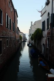 Back Alley Waterway In Venice, Italy. Vertical Shot With Glimpse Of Open Sea In Far Distance.