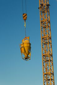 High Crane Concrete Machine For Spreading Cement Hoisted At Building Site On Blue Sky Background