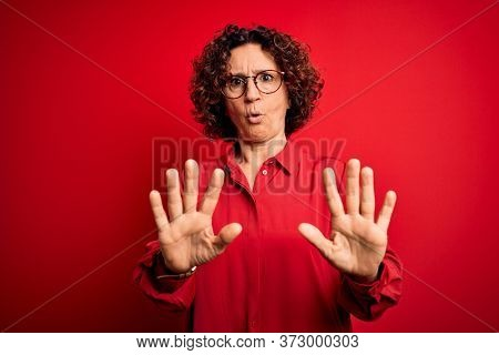 Middle age beautiful curly hair woman wearing casual shirt and glasses over red background Moving away hands palms showing refusal and denial with afraid and disgusting expression. Stop and forbidden.
