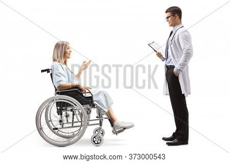 Full length profile shot of young female patient in a wheelchair talking to male doctor isolated on white background