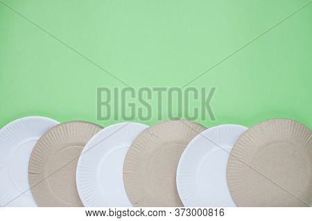 The Layout On A Green Background From Paper Disposable Plates. Caring For The Environment. Recycling