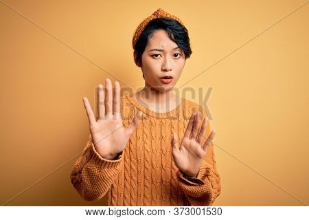 Young beautiful asian girl wearing casual sweater and diadem standing over yellow background Moving away hands palms showing refusal and denial with afraid and disgusting expression. Stop, forbidden.