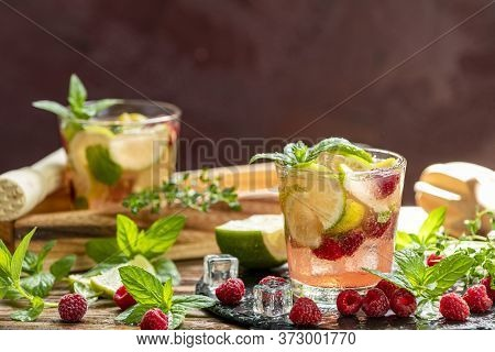 Refreshing Mint Cocktail Mojito With Rum, Lime, Mint, Thyme, Ice And Raspberry. Alcohol Or Non Alcoh