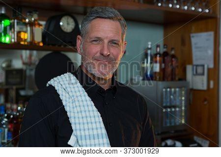 Portrait of bar tender standing at bar counter