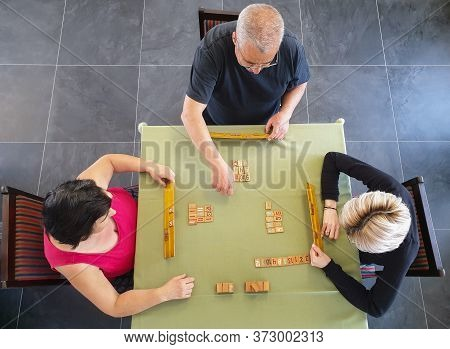 Family Of Three Playing Rummy Game On Table Inside. Indoor Home Isolation Activity, As Social Distan