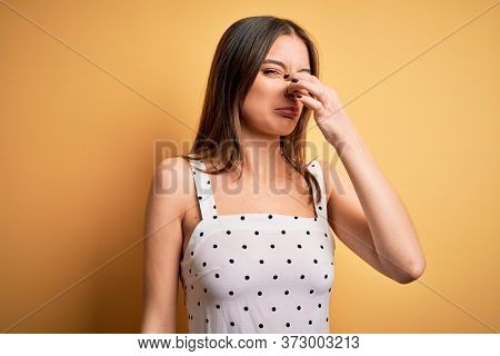 Young beautiful brunette woman wearing casual dress standing over yellow background smelling something stinky and disgusting, intolerable smell, holding breath with fingers on nose. Bad smell