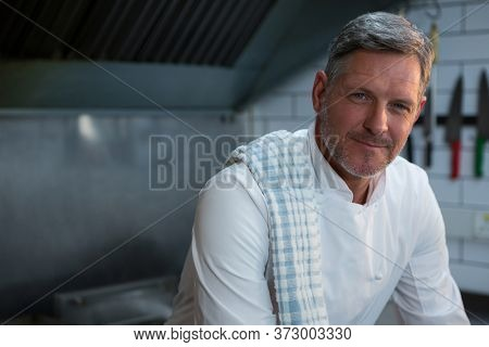 Portrait of male chef sitting in commercial kitchen