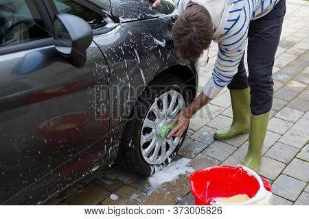 Male auto service staff washing a car tyre with sponge