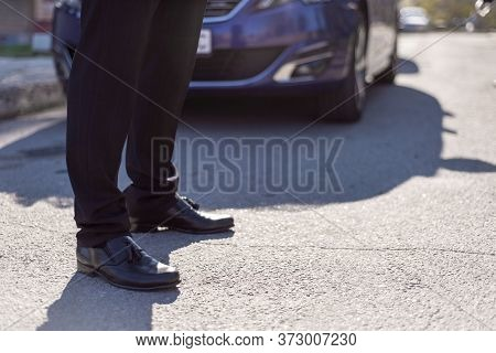Male Legs In Black Leather Shoes And Black Trousers, Against The Background Of A Silhouette Of A Car