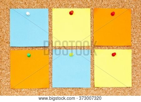 Six Blank Different Colors Sticky Notes Pinned On Cork Bulletin Board.