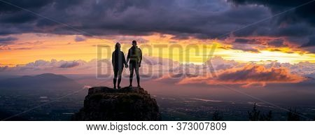 Fantasy Adventure Composite Of A Man And Woman Couple On A Rocky Mountain Peak During A Colorful Dra