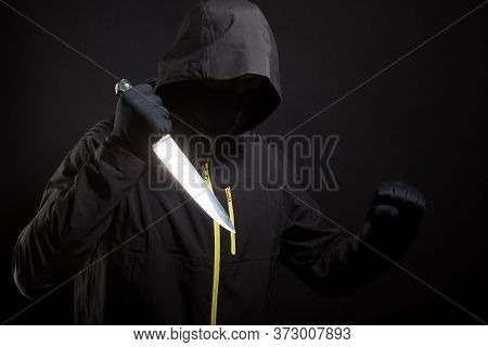 Killer In Black Holds The Knife In Aggressive Style. Selective Focus