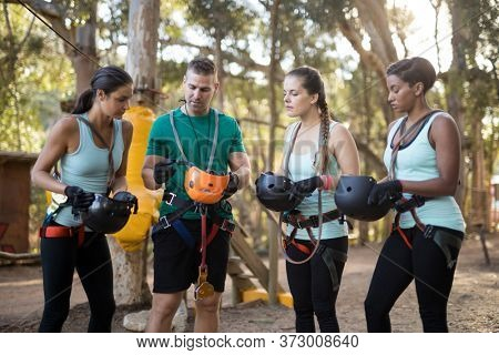 Coach interacting with trainee while wearing protective helmet in forest