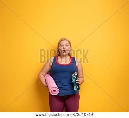 Fat Girl Does Gym At Home. Surprised Expression. Yellow Background