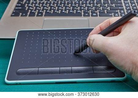 Hand Of An Artist With A Stylus Pen Using An Electronic Drawing Board To Work In A Graphics Editor P