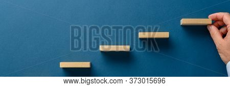 Wide View Image Of Businessman Hand Building Stairway Of Wooden Blocks Over Blue Background In A Con