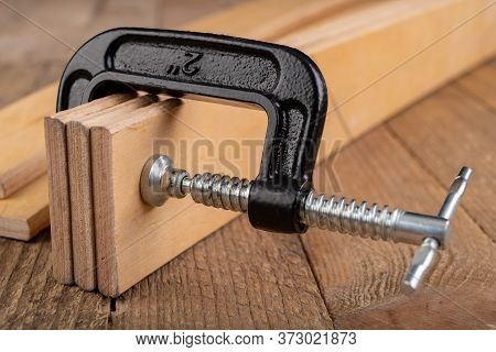 Carpentry Clamp Used For Gluing Wood. Carpentry Accessories In A Home Workshop.