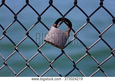 Silver Padlock Attached To Barbed Wire Fence On Waterfront