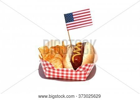 Hot Dog. Hot Dog with Mustard, Potato Chips and an American Flag. Isolated on white. Room for text. Hot Dogs are a perfect meal for any Holiday Lunch.