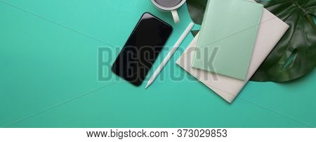 Creative Worktable With Smartphone, Diary Notebooks, Coffee Cup, Copy Space And Leaf Decorated On Ta
