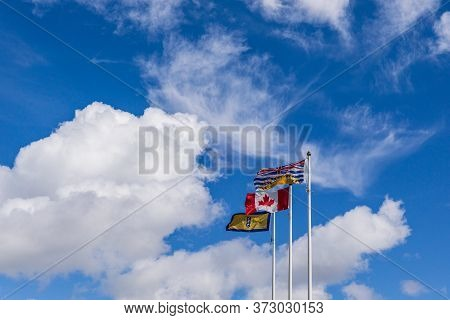 Flags Of Canada Richmond And British Columbia On Ploes Under A Blue Cloudy Sky.