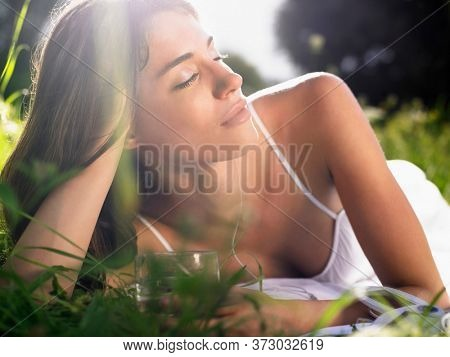 Young woman lying in meadow leaning on elbow with drinking glass