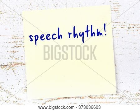 Concept Of Reminder About Speech Rhythm. Yellow Sticky Sheet Of Paper On Wooden Wall With Inscriptio
