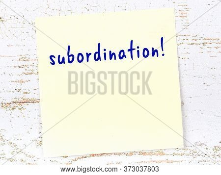 Yellow Sticky Note On Wooden Wall With Handwritten Inscription Subordination