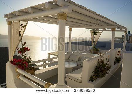 Gazebo In Warm Tones Overlooking The Bay Of The Greek Island Of Santorini