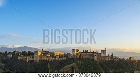 View Of Granada, Spain, Hilltop With Snow Capped Mountains In The Background