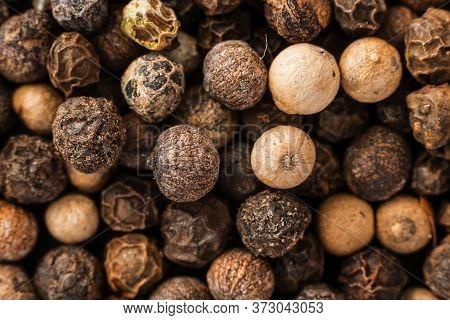 Closeup Dry Whole Black Pepper In Corns. Macro Background. Horizontal Shot For Wallpaper And Postcar