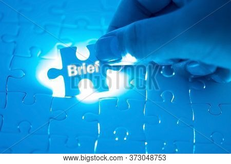 Brief Word On Jigsaw Puzzle. Businessman Hands Holding White Puzzle Business Concept. Business Conce