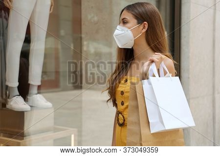 Portrait Of Young Fashion Woman With Protective Mask And Shopping Bags Looking Through Shop Window