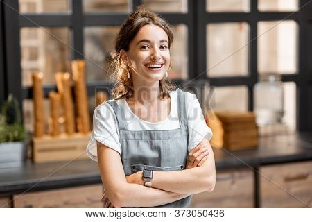 Portrait Of A Young And Happy Saleswoman At The Counter In Ice Cream Shop Or Cafe. Concept Of A Smal