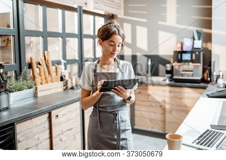 Young Saleswoman Working With A Digital Tablet At The Counter Of Cafe Or Confectionary Shop. Concept