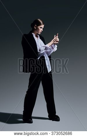 Fashion concept. Full length portrait of a gorgeous graceful young woman model posing in black velvet suit and white shirt on a gray background.